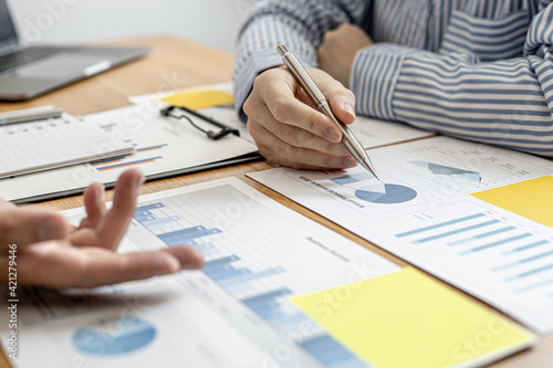 Fototapeta Two businessmen are meeting together on company finances, on a table where there is a paperwork for meetings, meetings and plans together for the company to thrive