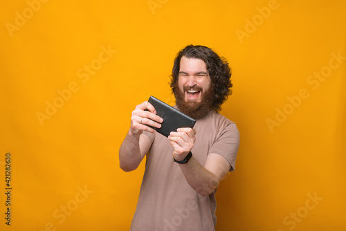 Obraz na plátně Cheerful young bearded man with curly hair playing games at tablet