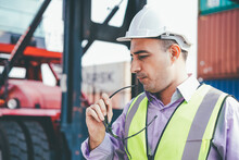 Caucasian Engineer Foreman Holding Sunglasses At Container Warehouse And Forklift Truck Background. Men At Work On Construction Site. Logistic Business Or Shipping Delivery