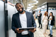 Happy african american male employee is standing in office hall, holding tablet in arms, browsing internet. Successful confident businessman looking at the camera, smiling