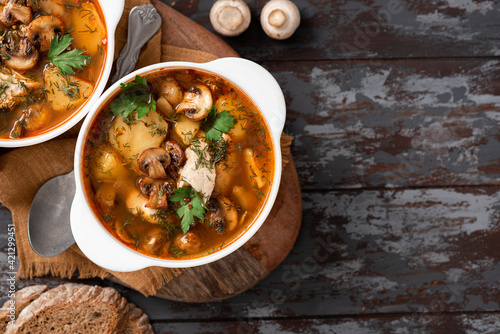 Fototapeta Mushroom soup top view. Hungarian mushroom soup with champignons, paprika, potatoes, meat, and spices in white bowls on a dark table. Tasty lunch or dinner. Free space for text obraz