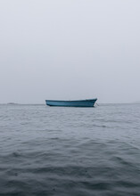 Ghost Ship Floating On Calm Waters With A Moody Sky