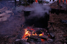 Camping, Late Evening. Food Is Cooked Over A Fire In A Metal Pot.