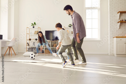 Mother trying to catch soccer ball having fun with adorable family at home. Sport activity and leisure fun during quarantine due to coronavirus pandemic. Happy caucasian parents and children together