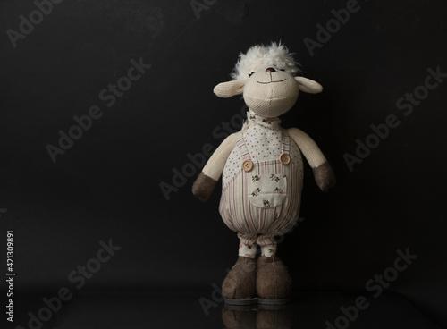 Fototapeta samotna owieczka maskotka na czarny tle z delikatnym odbiciem obraz