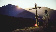 Rear View Of Man Praying In Front Of Cross On Mountain