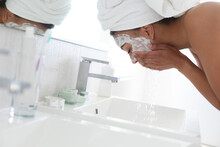 African American Woman Washing Off Her Face Mask In The Sink At Bathroom