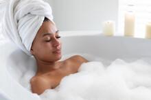 African American Woman Relaxing In Bathtub At Bathroom