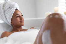 Thoughtful African American Woman Relaxing In Bathtub At Bathroom