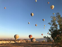 Hot Air Balloons Flying Over Landscape Against Sky