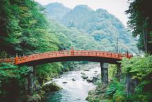 Arch Bridge Over Stream Against Mountains
