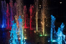 Illuminated Fountain In City At Night