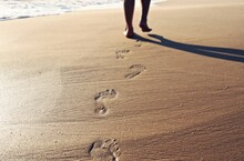 Low Section Of Person Walking On Shore At Beach Leaving Behind Footprints