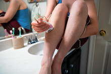 Young Woman Sitting And Shaving With Electric Cord Epilator, Removing Hair From Hairy Leg In Home Room Bathroom, Doing Skin Body Female Care