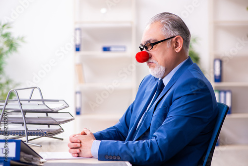 Fotografie, Obraz Old businessman clown working in the office