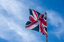 Low Angle View Of Union Jack Flag Against Blue Sky