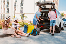 Friends Load Car Trunk With Baggage