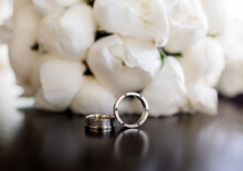 Front Close Up View Of Two Wedding Rings Lying On The Peonies Bouquet Background. Concept Of Details Of Wedding Ceremony.