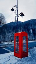 Classic Red British Telephone Box On The Snowy Street In Sinaia, Carpathian Mountains, Romania