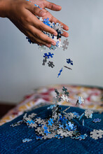Cropped Hands Throwing Jigsaw Pieces On Bed