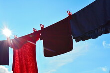 Low Angle View Of Textiles Hanging Against Blue Sky