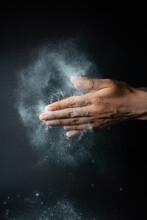 Close-up Of Woman Splashing Powder Against Black Background