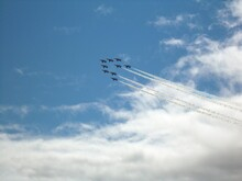 Low Angle View Of Red Arrows Flying Against Sky