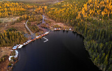Aerial View Of Wooden Houses By Lake In Forest