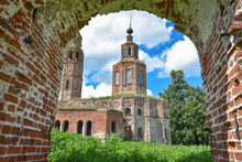 An Abandoned Dilapidated Church, Overgrown With Grass Against The Sky, Surrounded By Greenery, View Through The Arch