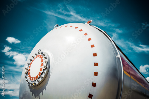 Fototapeta Truck with trailer, tank with flammable liquid, sunny day outside, metallic colo