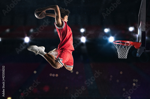 Fotografija Basketball player in red uniform jumping high to make a slam dunk to the basket