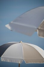 Close-up Of White Umbrella Against Clear Blue Sky