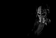 Portrait Of Spooky Man Wearing Mask Pointing Against Black Background
