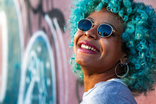 Portrait Of Young Smiling Black Afro American Woman With Blue Hair And Sunglasses Outdoors