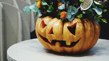 Close-up Of Pumpkin With Flowers On Table. Halloween