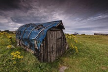 Upturned Boat Shed On Field Against Moody Sky