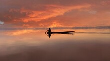 Silhouette Person In Boat Against Sky During Sunset
