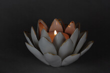 Lit Tea Candle With Flame In A Ceramic Lotus Flower Candle Holder On A Dark Gray Background With Dramatic, Romantic Lighting And Copy Space