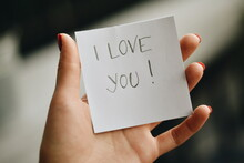 Close-up Of Hand Holding Paper With Love Text