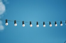 Low Angle View Of Light Bulbs Hanging Against Blue Sky