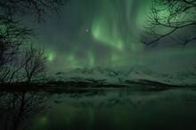 Scenic View Of Aurora Borealis Over Lyngen Alps And Lake