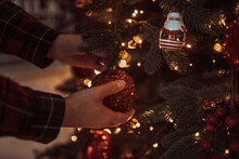 Cropped Hand Of Man Touching Ornaments On Christmas Tree