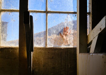 Woman's Hand In Window Of Abandoned Barn