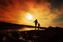 Silhouette Of Couple Standing On Beach At Sunset