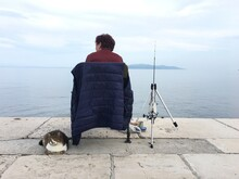 Rear View Of Lady And Cat Looking At Sea Against Sky  - Catch Me If You Can