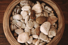 Close Up Decorative Stones Of Different Beige Shades On A Wooden Plate. Top View