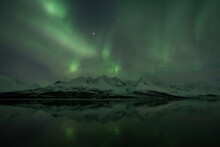 Scenic View Of Aurora Borealis Over Lyngen Alps And Lake