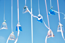 Colorful Water In Plastic Bags With Ribbons On The Blue Sky