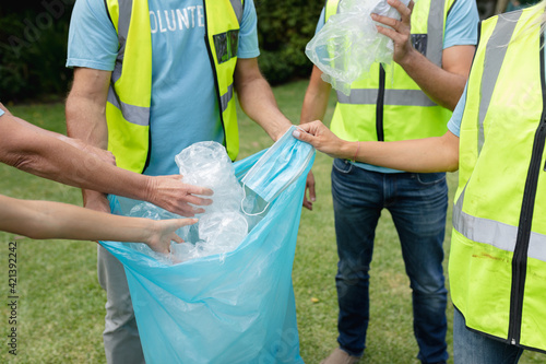 Fototapeta premium Midsection of caucasian multi generation group collecting plastic rubbish and face mask in field