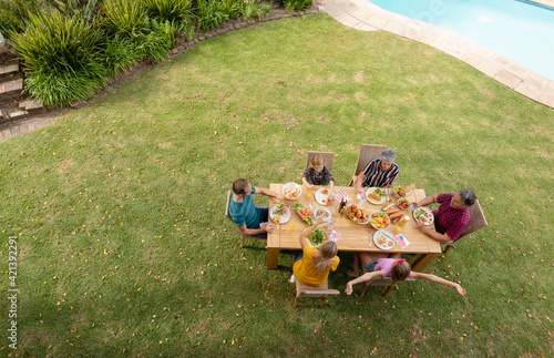 High angle view of caucasian three generation family sitting at table eating meal in garden
